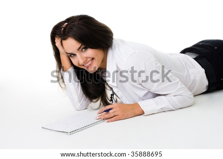 Woman laying on the floor with note book smiling and laughing, isolated on white - stock photo