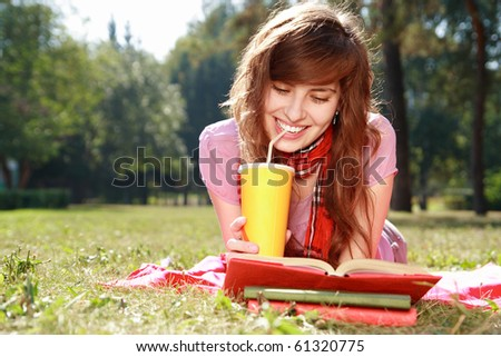 woman lays on a grass, reads the book and drinks from a paper cap