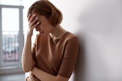Woman lean on wall, touching face, feeling sad and stress, worried and anxious. Depression due to loneliness, break up, unemployment or bad news, in fear and panic. Psychology concept