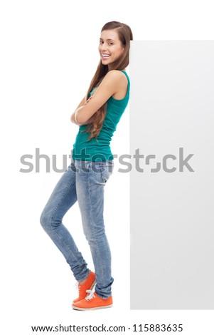 Woman leaning against blank billboard
