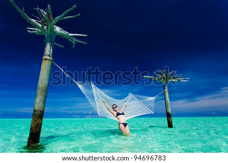 Woman leaning on over-water hammock in the middle of tropical lagoon