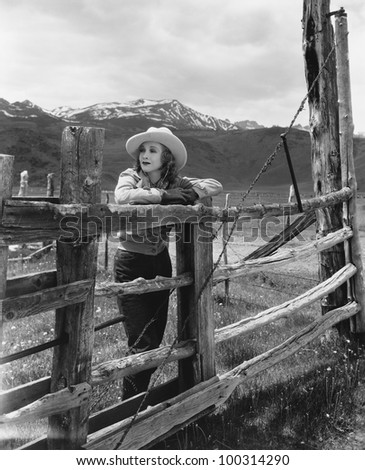 Woman leaning on wooden fence on ranch