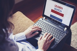 Woman learning dutch through internet with a laptop at home