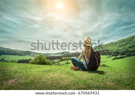 Woman leasure and relaxing around the mountains with beautiful green fields view under sunlight on summer day.