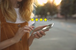 Woman leaving review online via smartphone outdoors, closeup. Four out of five stars over gadget