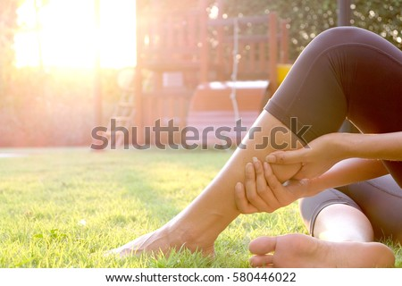 Woman leg pain, leg pain Sitting up on the grass in the playground. The morning sun light, healthy concept. #580446022