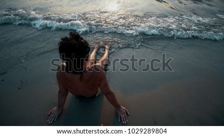 Woman legs and bare feet sitting on golden sand beach at sunset and looking at ocean water seaside #1029289804