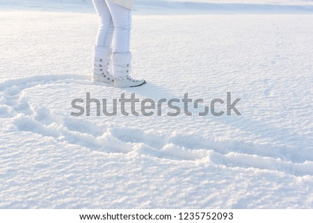 Woman legs dressed in snow boots with footsteps in deep snow. Winter background with copy space. #1235752093