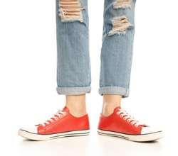 Woman legs feet jeans red sneakers hipster style on a white background. Isolation
