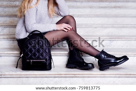 Woman legs in black ankle boots with bag. Trendy hipster outfit style - Shutterstock ID 759813775