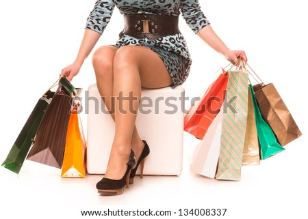 Woman legs in highheels with many shopping bags isolated on white background. Shopping concept.