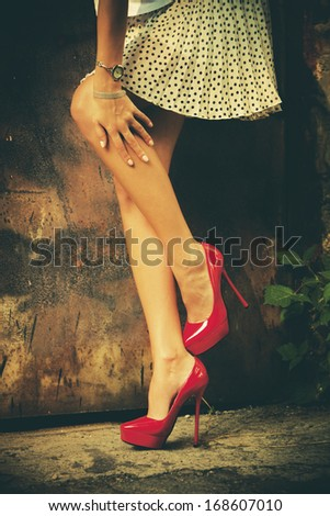 woman legs in red high heel shoes and short skirt outdoor shot against old metal door