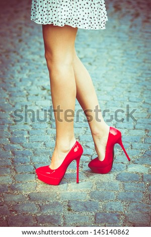woman legs in red high heel shoes and short skirt outdoor shot on cobble street