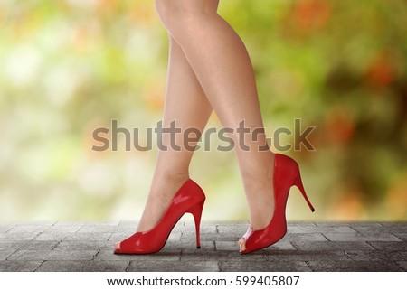 Woman legs in red high heels walking on urban street