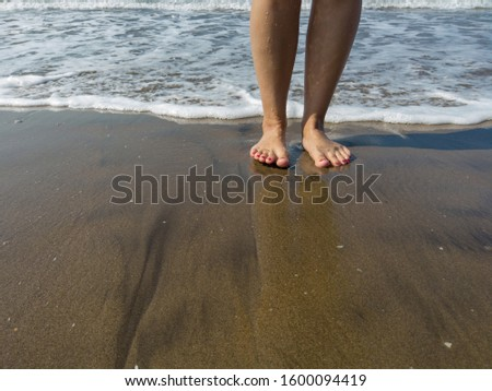Woman legs in sea water. Closeup of woman legs on sea shore. Summer, beach, leisure and body part concept - closeup of woman legs on sea shore