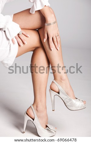 woman legs in silver high heels shoes, studio shot