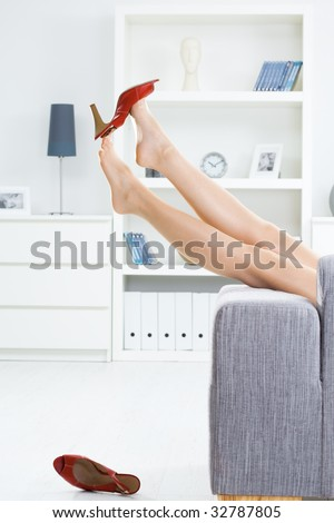 Woman legs in stockings, taking off high heel shoes.