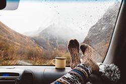 Woman legs in warm socks on car dashboard. Drinking warm tee on the way. Fall trip. Rain drops on windshield. Freedom travel concept. Autumn weekend in mountains.