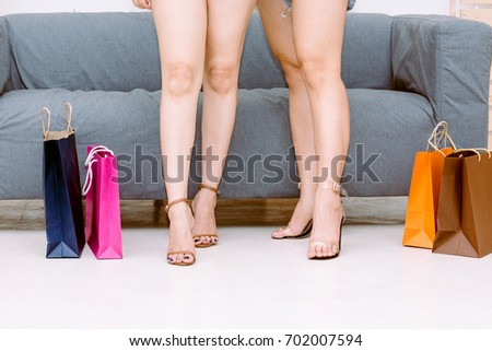 Woman legs near colorful shopping bags