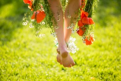 Woman legs on green grass with flower dress. Summer vacation concept. backlit