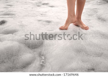 Woman legs on the white mineral surface in Pamukkale (Turkey)