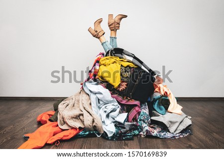 Photo of  woman legs out of a pile of clothes on the floor. shopping addiction concept