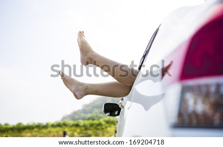 Woman legs out the windows in car above the clouds (Summer road trip car vacation concept)