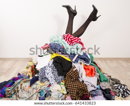 Photo of  Woman legs reaching out from a big pile of clothes and accessories. Woman buried under an untidy cluttered woman wardrobe. Woman in high heels needs help from to much shopping. Shopaholic girl.
