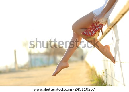 Woman legs silhouette with high heels hanging of her hand and sitting on a wall
