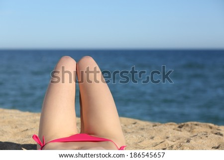 Woman legs sunbathing on the beach with the horizon in the background