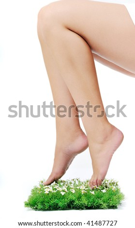 woman legs walking on small peace of green grass isolated on white representing last oasis concept - stock photo