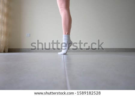 Woman legs wearing pink leggings and white sock standing on toes in floor room background.