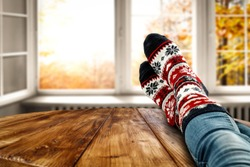 Woman legs with autumn socks and open fall window. Wooden board of free space for your decoration and golden leaves.