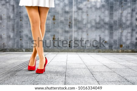 Woman legs with red shoes and wall of free space for your decoration.  #1016334049