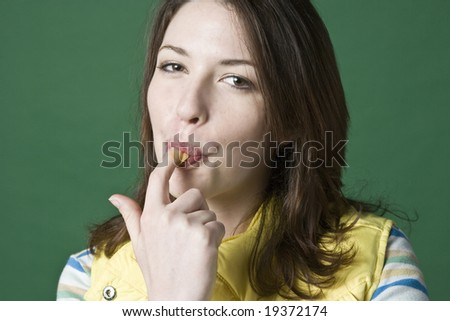 Woman licking peanut butter from her finger