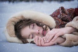 Woman lie around in soft snow on a winter day, rejoicing the snowfall.