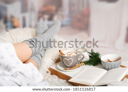 Woman lies with Cup; Kako; Hot chocolate; marshmallows; Book tray; Bed; Sofa; Blanket; Snuggle blanket; Fur; Fireplace; Wind light; Indoor; Living room; Cosy; Reading; Enjoying; Relaxing; Winter time Stockfoto ©