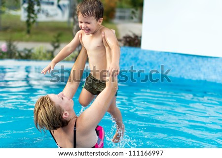 Woman lift up her son in the swimming pool