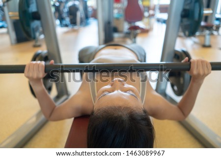 Woman lifting barbell, working with barbell and her arms and chest at gym.
