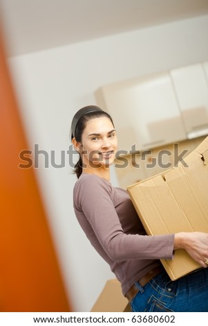 Woman lifting cardboard box while moving home, smiling.?
