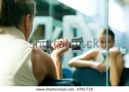 Woman lifting dumbbells in a gym, seeing herself in a mirror (focus only on the dumbbell)