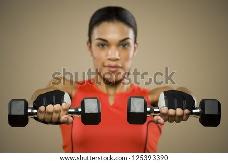 Woman lifting dumbbells in gloves
