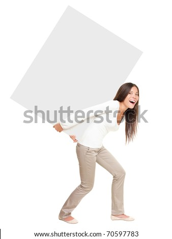 Woman lifting / showing heavy blank billboard sign. Woman carrying empty sign board on her back. Funny image of beautiful asian  caucasian female model isolated in full length on white background.
