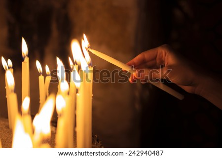 woman lighting candles  in a church #242940487