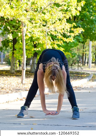 Woman limbering up for exercises bending down towards the ground with her hands clasped to stretch her muscles