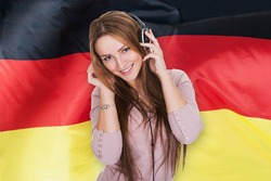 Woman Listening German Learning Audiobook In Front Of German Flag