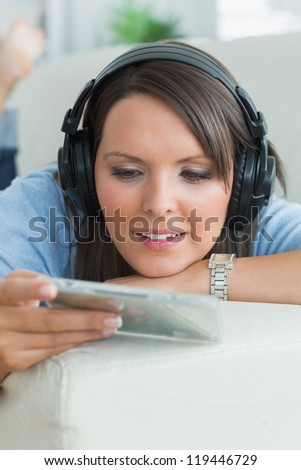 Woman listening music and looking at cd on sofa in the living room