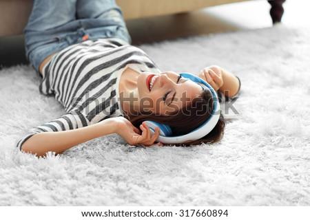 Shutterstock Woman listening music in headphones on carpet in room