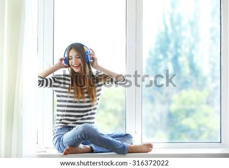 Woman listening music in headphones on windowsill background