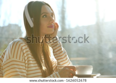Woman listening to audiobook at table in cafe Stockfoto ©